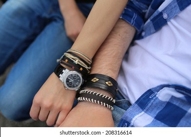 Close up image of woman's and man's hands with watch and different bracelets