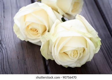 Close up image of yellow roses on a wooden background.