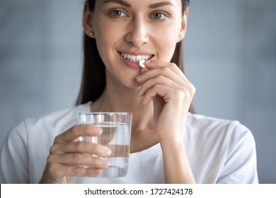 Close up image young adult beautiful 35s woman smiles takes pill holding glass of water, concept of minerals and vitamins for female, hair skin nail care dietary supplement, daily dosage of medication