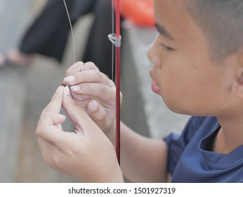 Close up image of young Asian boy put a worm on a hook, worm fishing day