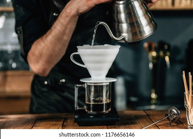 Close up image of young male barista pouring boiling water from kettle to drip coffee maker on wooden table. Barista wearing dark uniform.
