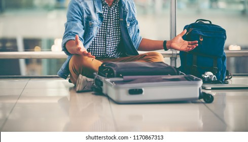 Close up image of young traveler man sitting on the floor at the terminal airport  finding something  lost . Unhappy man lost something on his trip,traveling concept,selective focus,copy space.