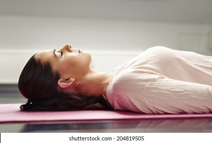 Close up image of young woman lying on a yoga mat with her eyes closed in meditation.