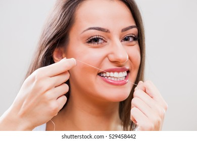 Close up image of young woman who is using dental floss.
