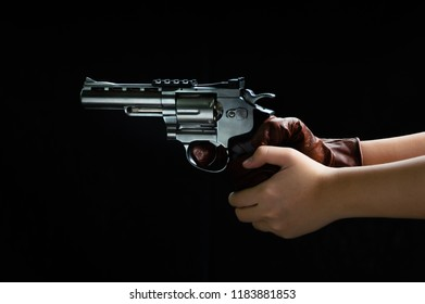 Close up images of The gun in his hand ready to shoot, with black blackground to weapon and crime concept.