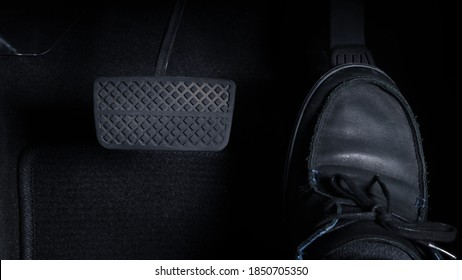 Close up images of man driving car by pushing accelerator and brake pedal with right foot black leather shoe and black jean pant. camera shot inside the japanese car.