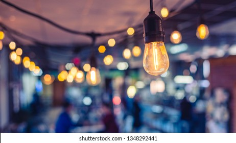 close up of incandescent light bulb hanging from the roof of a café with blurred background containing two patrons sitting at table together