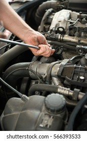 Close up of incognito mechanic hands holding a tool while working on car engine
