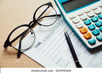 Close up income tax return planning ,1040 tax form, with calculator, pen and eye glasses place on the wooden table.