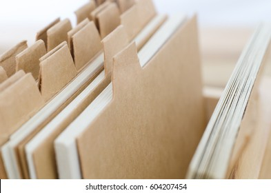 Close up of index cards with plain light brown dividers left blank to provide copy space. Elevated and angled side view.
