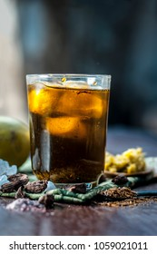 Close up of Indian and Asian famous mango juice AAM PANNA in a transparent glass with ice cubes and cardamoms,sugar,black salt and jaggery.