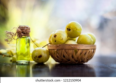 Close up of Indian gooseberry with its extracted essence or concentration in a transparent bottle on wooden surface with raw amla in a fruit and vegetable basket.
