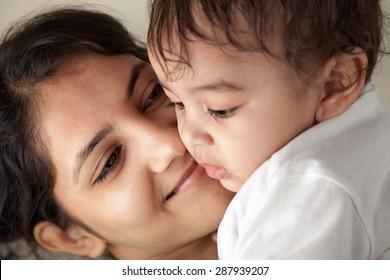 Nahaufnahme einer glücklichen indischen Mutter, die ihr Baby mit Liebe anschaut