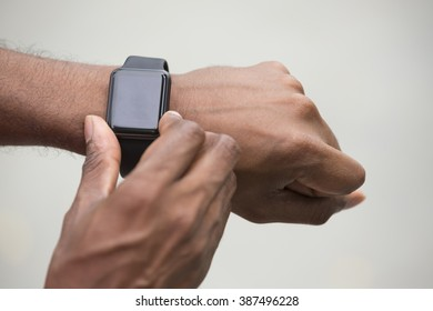 Close up of an Indian man looking at his smart watch heart rate monitor. Asian man using a smart watch.