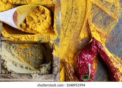 Close up of Indian spices of Turmeric powder, coriander powder and chili powder in  a wooden box with a spoon.
