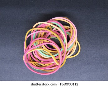 Close up of Indonesian colorful rubber band or plastic band isolated on black background. The color are yellow, green red, orange.
