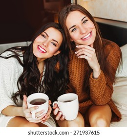 Close up indoor lifestyle portrait of two pretty cheerful   girls  holds  cup of coffee .   Sisters hugs and have great time together in the morning  time.