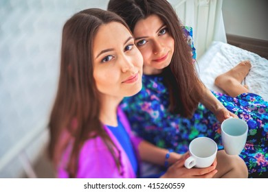Close up indoor lifestyle portrait of two pretty cheerful girls holds cup of coffee .