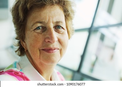 close up indoor portrait of 70 years old senior woman