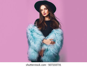 Close up indoor studio fashion portrait of gorgeous  woman in stylish winter fluffy  blue coat and black hat posing on bright pink background .Spa?e for text.