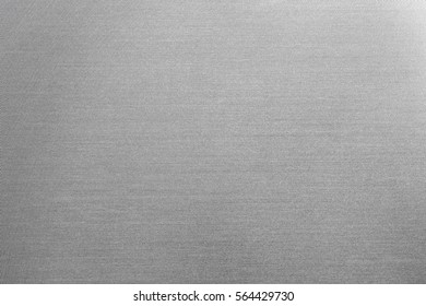 Close up industrial background of fractally scratched diagonal circular lines to silver metal/stainless steel surface. Creative lighting detail macro photography.