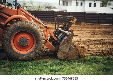 Close up of industrial bulldozer scoop moving earth and doing landscaping works