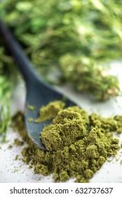 close up of industrial hemp protein powder with hemp tea in background