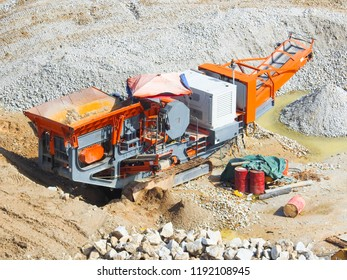 Close up  of industrial mechanical conveyor belt or rock crusher working on construction site. Selective focus and crop fragment