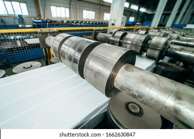 Close up industrial steel roll coil for metal profile forming machine in metalwork factory workshop. Metal rolls, concept for metalwork production.