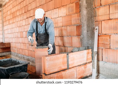 Close up of industrial worker, bricklayer installing bricks on interior building at construction site