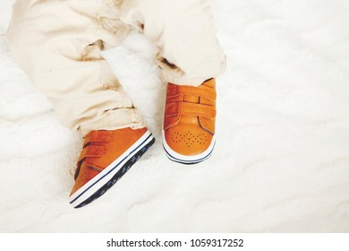 Close up of infant boy in fashion brown leather kids shoes and denim pants. Stylish first cute little baby shoes