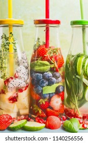 Close up of infused water in bottles with drink straw and ingredients, front view. Water Flavored with colorful fruits, berries and herbs. Summer drinks. Healthy and clean detox beverages.