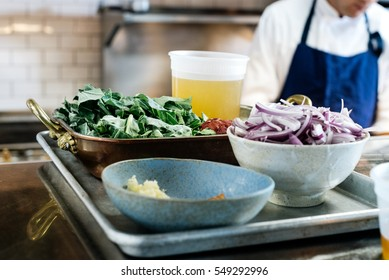 Close up of ingredient bowls in mise en place restaurant scene with chopped garlic, oil, red onion, ham hock and collard greens in copper casserole dish with chef's coat and apron in the background.