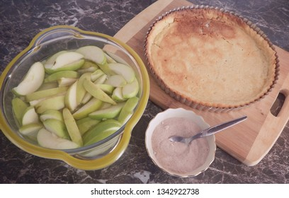 close up of ingredients for an apple tart. Sliced apple, a small bowl of sugar, a baked pastry shell. some in monochrome.