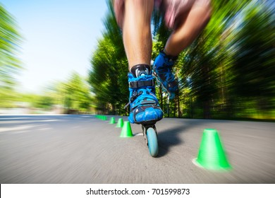 Close up of Inline roller skater on a slalom course.