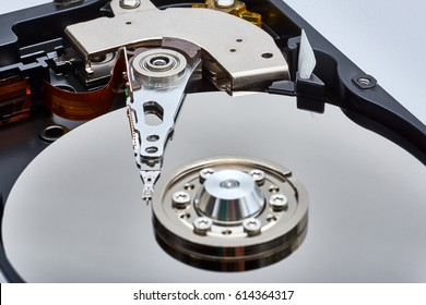 Close up inside of Hard disk drive (HDD) . Detail of writing/reading head on acuator arm and axis, spindle and platters