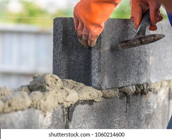 Close up of installing bricks in construction site by industrial bricklayer.