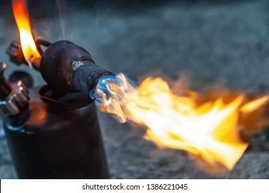 Close up of a instrument gas burner flame burns orange machine