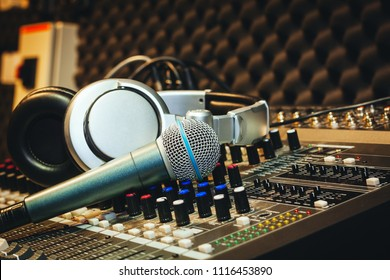 Close up instruments music background concept.Single microphone with headphones on sound mixer board in home recording studio.Free space for creative design text & wording mock up template wallpaper.
