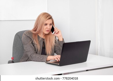 Close up of an interested businesswoman in a suit working at her white office. She is talking on phone and work with laptop