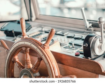 Close up of the interior of a large motor boat. The steering wheel and motor controls can be seen and the boat harbor slurred through the glass boat window.