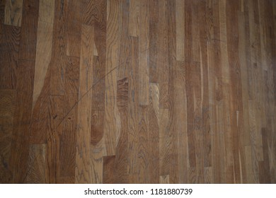 Close up interior view of wooden parquet floor. Pattern of bright clear brown rectangular planks. Flat surface with light reflection. Abstract architectural picture taken in a french dance hall.