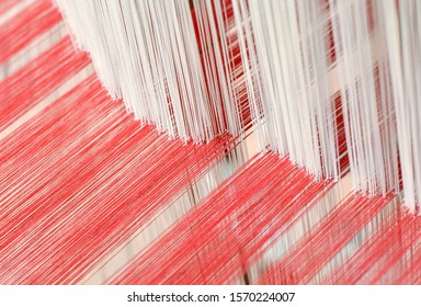 Close up of interlacing between white warp yarn and red weft yarn on traditional cotton weaving loom. Selective focus.