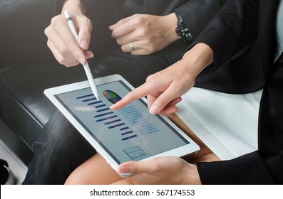 close up investor businesswoman hand finger point on tablet pad display for consult stock statistic graph with businessman for business technology concept