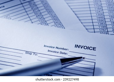 Close up Invoice Documents and Pen on Top of Table, Emphasizing Invoice Number and Date.