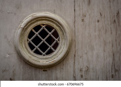 Close up of a ironwork peephole on a medieval wooden door.
