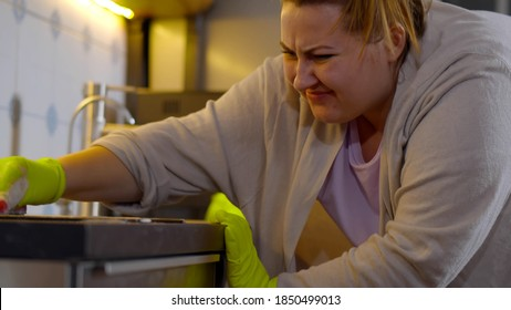 Close up of irritated young fat woman trying to wipe dirty spot on countertop with sponge. Overweight housewife on rubber cloves cleaning kitchen after cooking dinner