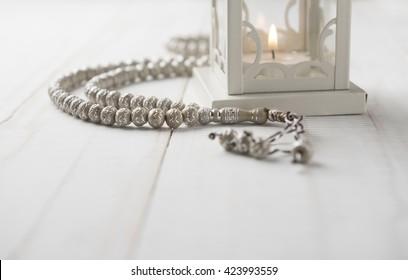 Close up of Islamic prayer beads near candle holder on white background.