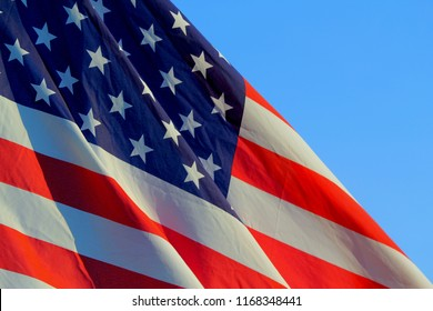 Close up isolated colorful undulating United states of American U.S. flag with stars and stripes red white and blue 4th of July blowing in the wind at sunset.