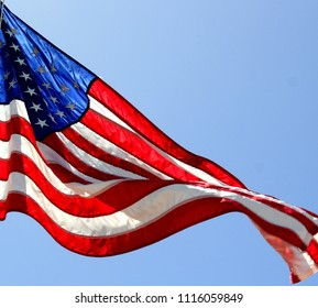 Close up isolated colorful United states of American U.S. flag with stars and stripes red white and blue against a blue sky